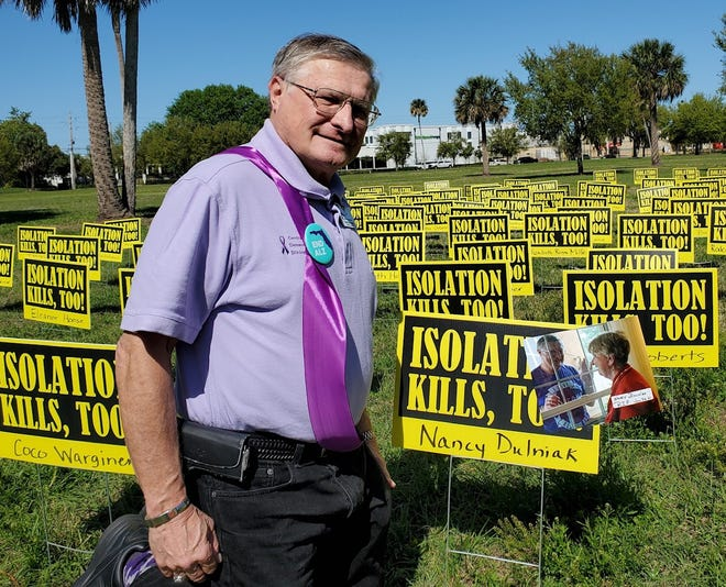 """Dennis Dulniak helped set up a poster display for the """"Isolation Kills, Too"""" campaign in Orlando, Fla. He advocates for nursing home visitation rights after the death of his wife, Nancy, this year. Restrictions during COVID-19, he says, """"robbed me of my access to her."""""""