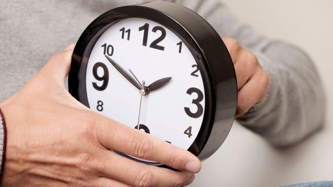 A man winds back the clock.