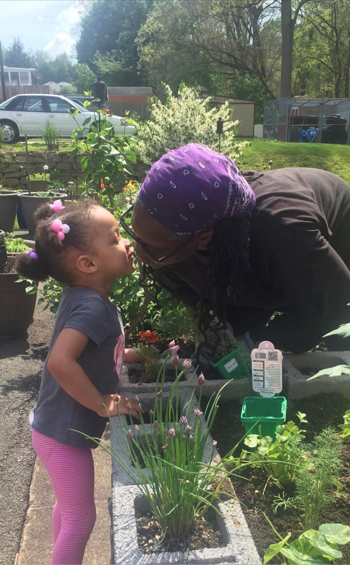 """""""Gardening allows me to commune with my ancestors. It allows me to commune with Mother Earth. It allows me to commune with God,"""" said Janet Carter, 61, seen here with her granddaughter."""