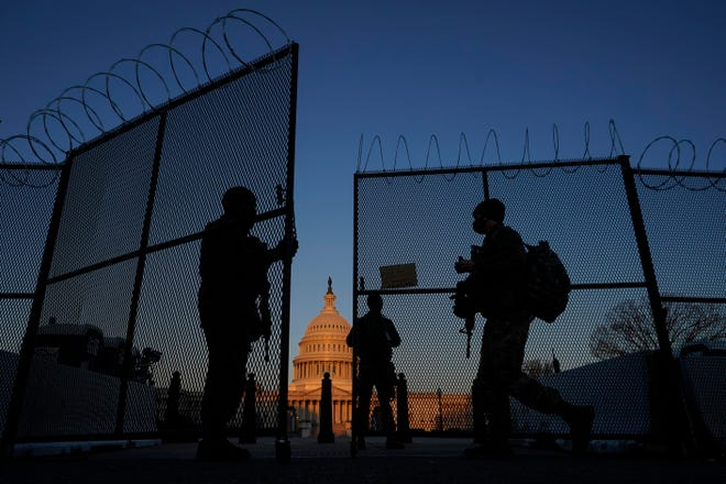 Members of the National Guard open a gate in the razor wire-topped perimeter fence around the U.S. Capitol on Monday, allowing another member in at sunrise.