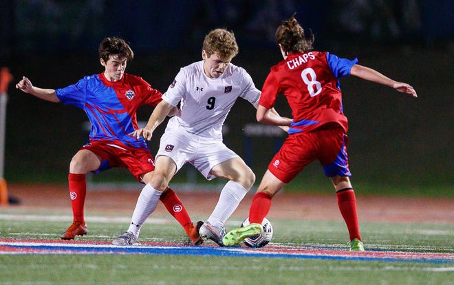 Lake Travis forward Alex Bethke, center, battles for the ball between Westlake's Graham Jatinen, right, and Ayerai Gonzalez during the the teams' 1-1 draw Friday at Westlake High School. Bethke scored the No. 1 Cavs' lone goal in the contest.