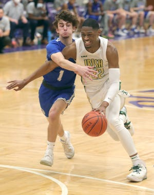 St. Vincent-St. Mary senior Malaki Branham is fouled by Gilmour Academy defender Jerome Todd during the Irish's 67-40 win in a Division II regional championship game. [Phil Masturzo/Beacon Journal]
