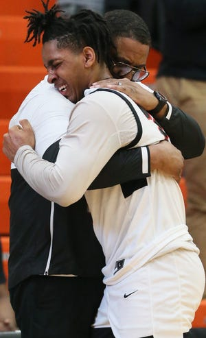 Buchtel's Noah Peeples is comforted by coach Rayshon Dent as he comes off the court late in the second half of the Griffins' 88-74 loss to Lima Shawnee in a Division II regional final Saturday at Elida High School. [Mike Cardew/Beacon Journal]