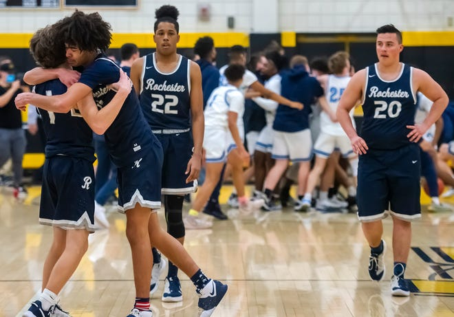 Rochester's J.D. Azulay consoles teammate Devon Hemer after their WPIAL championship loss to Bishop Canevin Friday at North Allegheny High School. Teammates Noah Haskins (22) and Ryan Zawislak (20) leave the court as the Crusaders celebrate behind them.