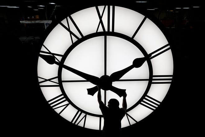 Electric Time technician Dan LaMoore adjusts a clock hand on a 1000-lb., 12-foot diameter clock constructed for a resort in Vietnam, Tuesday, March 9, in Medfield, Mass. Daylight saving time began at 2 a.m. local time Sunday, March 14, when clocks were set ahead one hour.