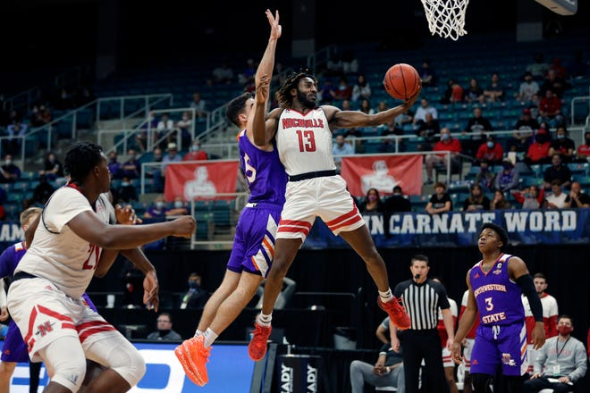 Nicholls State guard Andre Jones (13) shoots next to Northwestern State guard Jovan Zelenbaba, center left, during the second half of an NCAA college basketball game in the Southland Conference semifinals Friday, March 12, 2021, in Katy, Texas. (AP Photo/Michael Wyke)