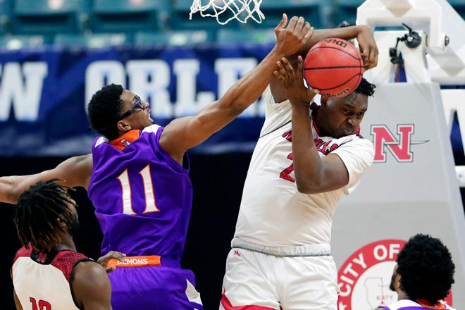 Northwestern State forward Jamaure Gregg (11) reaches to knock away the rebound from Nicholls State center Ryghe Lyons (21) during the first half of an NCAA college basketball game in the Southland Conference men's tournament semifinals Friday, March 12, 2021, in Katy, Texas. (AP Photo/Michael Wyke)