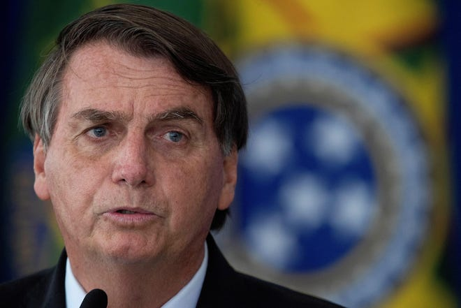 Brazilian President Jair Bolsonaro reacts while sanctioning the bills that expand the capacity to purchase vaccines by the Federal Government, at the Planalto Palace, in Brasilia, Brazil, March 10 2021. Brazil reported 85,663 new cases on Friday, pushing the total to 11,363,380 and surpassing India in coronavirus infections, retaking the post of second hardest-hit country in the world.