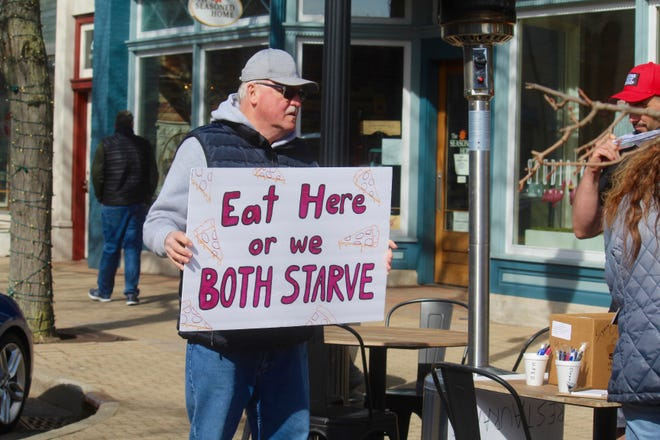 Jim Storey, an Allegan County commissioner, holds a sign during an Allegan County Republican Party demonstration organized to draw attention to restaurant owners dealing with capacity restrictions in place due to the COVID-19 pandemic.