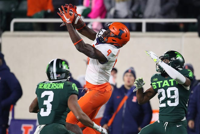 Josh Imatorbhebhe (9) of the Illinois Fighting Illini catches a fourth quarter fourth down pass to keep the drive alive between Xavier Henderson (3) and Shakur Brown (29) of the Michigan State Spartans at Spartan Stadium on Nov. 9, 2019 in East Lansing, Michigan.