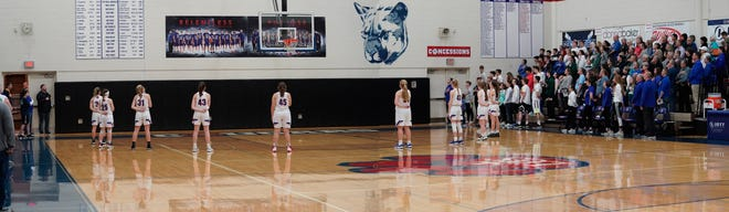 Lenawee Christian girls basketball team stands around the 3-point line for the national anthem prior to a Division 4 regional semifinal in 2020.