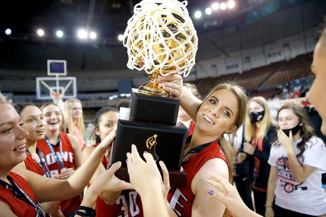 Howe's Caitlyn Stacy holds the gold ball trophy after winning the Class 2A girls basketball state title Saturday against Silo at State Fair Arena in Oklahoma City.