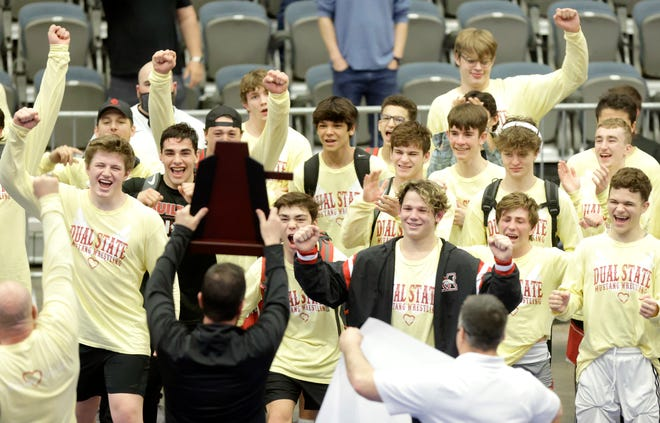 Mustang wrestlers celebrate as they are presented the Class 6A dual state championship trophy at Stride Bank Center in Enid on Saturday.