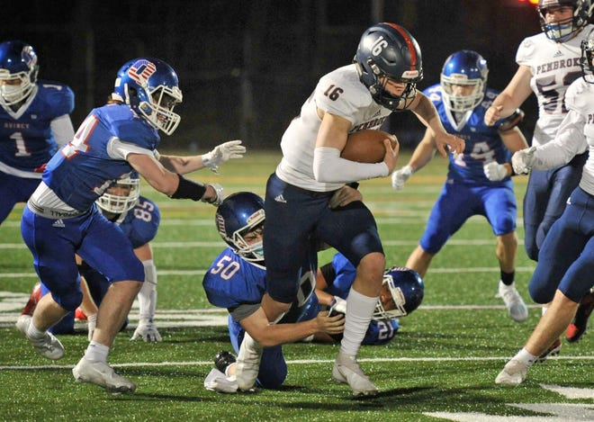 Pembroke quarterback Drew Hall carries as he is about to be brought down by Quincy's Will Ploof, left, and teammate Alex Rheault, center, during high school football at Veterans Stadium in Quincy, Friday, March 12, 2021.