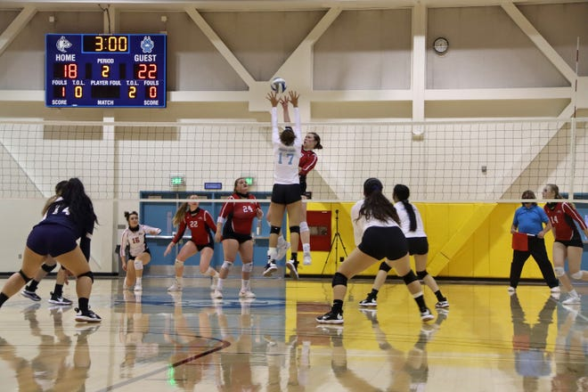 Lorna Pizzarro (17) puts up a block against Bakersfield College's Tia Jules (18) during Thursday night's game at Cerro Coso Community College.