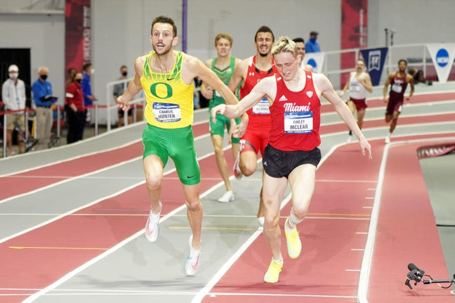 Oregon's Charlie Hunter, left, outleans Finley McClear of Miami (Ohio) to win the 800 meters Saturday in helping lead the Ducks to the team title at the NCAA Indoor Track and Field Championships at the Randal Tyson Center in Fayetteville, Arkansas.