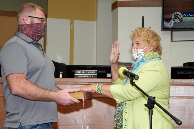 With her son Jake White holding the Bible, Alice White recites the oath of office Saturday morning at North Port City Hall during her swearing in as the new District 1 representative on the North Port City Commission.