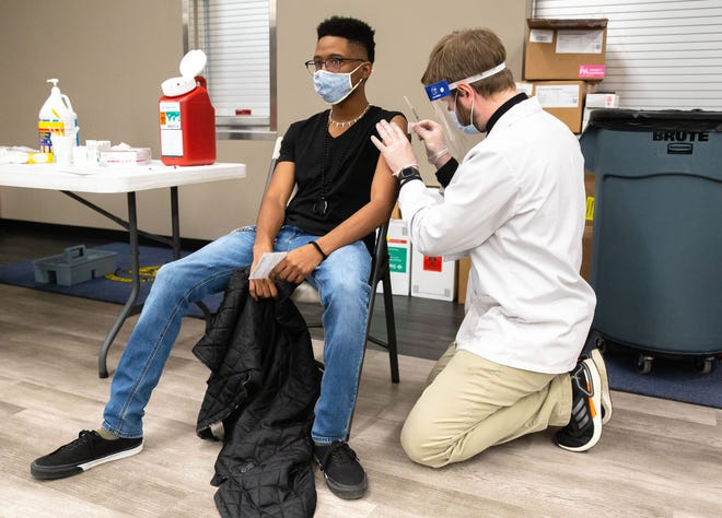 Malachi Wilson, 19, receives the COVID-19 vaccine from Walgreens Pharmacist Brendan Spence, during a vaccine distribution at The Salvation Army in Springfield, Ill., Saturday, March 13, 2021. Walgreens partnered with Sangamon County, Capital Township and The Salvation Army to distribute 800 doses of the Johnson & Johnson COVID-19 vaccine during a distribution on Saturday and Sunday at The Salvation Army on East Clearlake Ave. [Justin L. Fowler/The State Journal-Register]