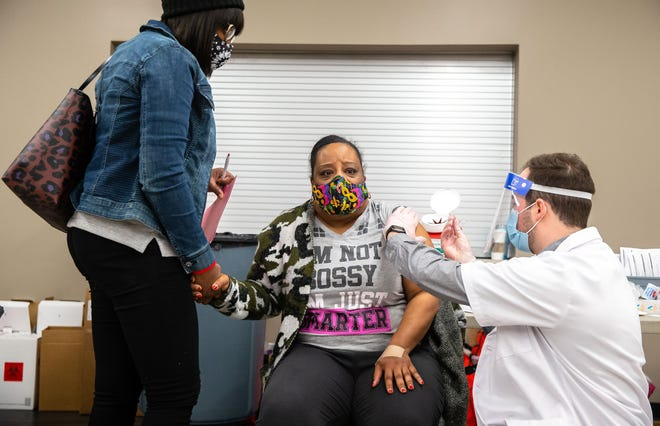 Katrina Freemon holds the hand of her sister Tanya Rolfe, left, a family nurse practitioner, as she receives the COVID-19 vaccine from Walgreens Pharmacist Dayton Trent during a vaccine distribution event at the Salvation Army in Springfield, Ill., on Saturday.