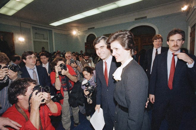 Massachusetts Gov. Michael S. Dukakis, center, with his wife Kitty, stands before the press, Monday, March 16, 1987, at the statehouse in Boston after announcing his intention to be a candidate for the 1988 Democratic presidential nomination.
