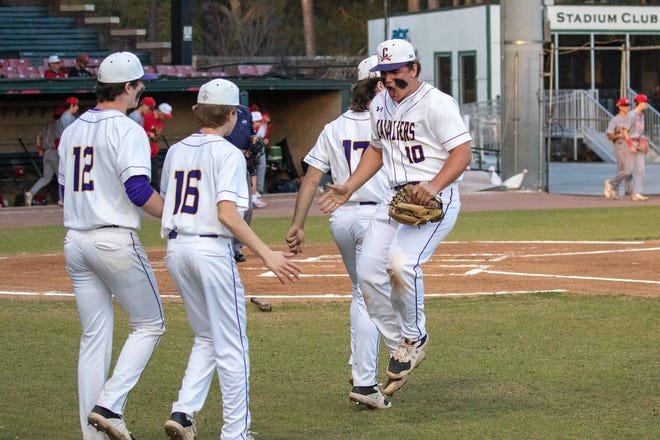 Calvary Day's Will Hampton (10) celebrates with his teammates after a double play to end the first inning against Savannah Christian on Friday at Grayson Stadium. Calvary Day won 5-4 in 10 innings.