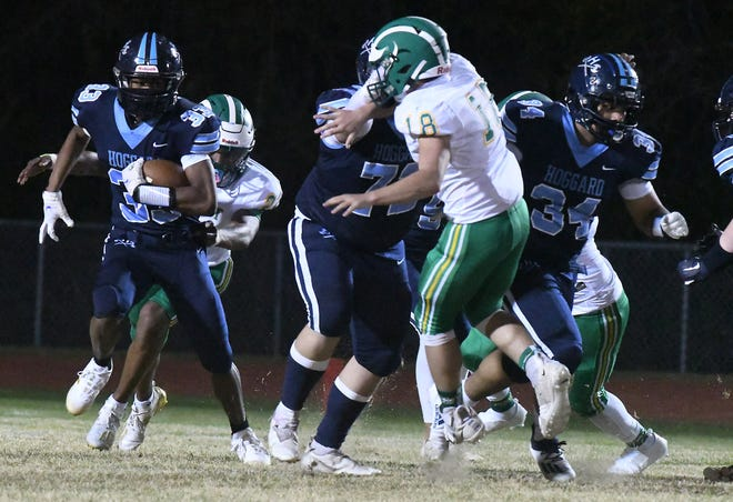 Hoggard's #33 Sam Williams takes off for a few yards as Hoggard took on West Brunswick Friday March 12, 2021 at Hoggard High School in a MEC football game. Hoggard shut out West Brunswick 27-0.   [KEN BLEVINS/STARNEWS]