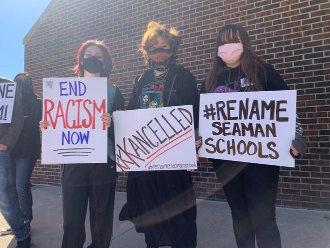 Students show off their posters at a protest out of the Seaman Education Center on Feb. 28, 2021. Students, backed by other groups of alumni and teachers in the district, are calling on the Seaman Board of Education to change the district's name, which they argue inappropriately honors a man who was a leader in the Topeka KKK.