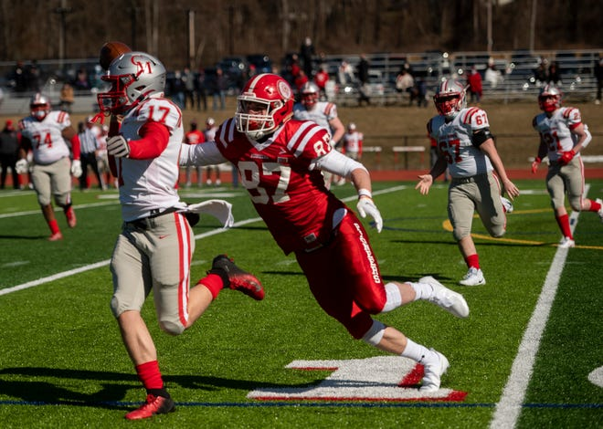 St. John's linebacker Quinn Herlihy chases down Catholic Memorial quarterback JC Petrongelo during last week's season opener in Shrewsbury.