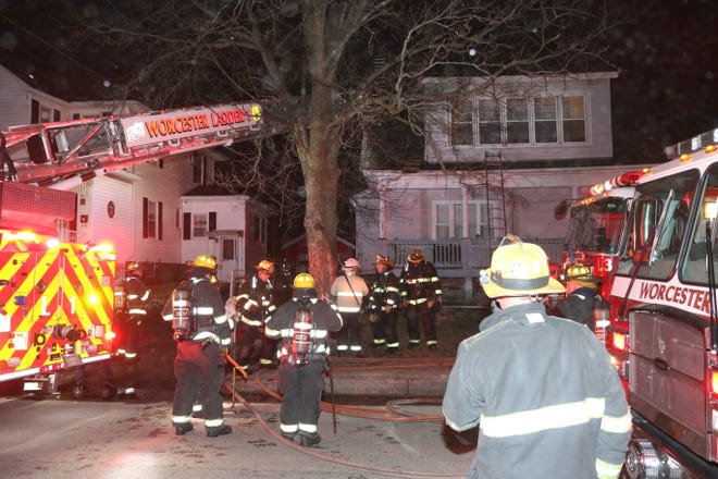 Firefighters work at the scene of a two-alarm fire on Northboro Street in Worcester on Friday night.