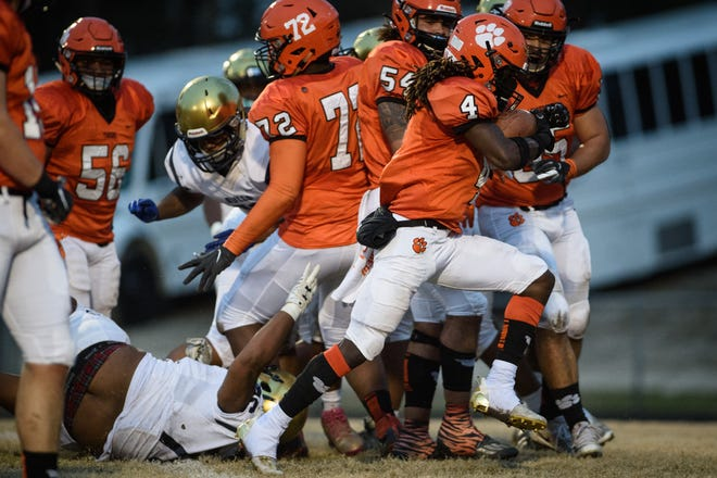 Raheem Baldwin runs through traffic during the E.E. Smith at South View football game on Friday, March 12, 2021.