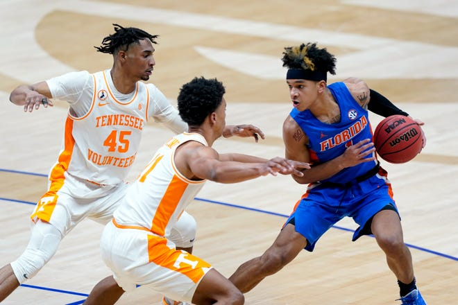 Florida's Tre Mann (1) is defended by Tennessee's Keon Johnson (45) and Jaden Springer (11) in the first half Friday in the Southeastern Conference Tournament quarterfinal in Nashville, Tenn.