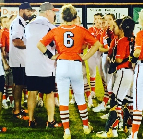 Trenton softball coach Todd Bryant huddles with his team after knocking off No. 4 Dixie County 3-1 Friday night.