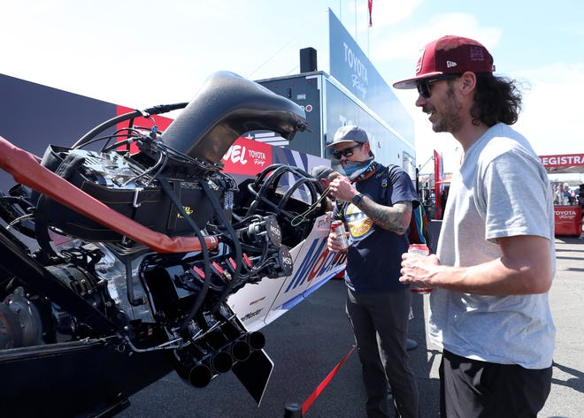 Cale Armantrout, right, and his brother Seth, who are at Gatornationals for their first time, check out the mock up Top Fuel Dragster at the Toyota Racing booth during the Amalie Motor Oil NHRA Gatornationals at the Gainesville Raceway in Gainesville on Saturday. [Brad McClenny/Gainesville Sun]