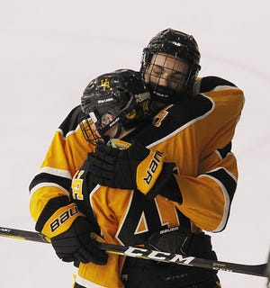 Upper Arlington's Rory Brennan (facing) and  Noah Domagalski console one another after a 3-0 loss to Lakewood St. Edward in a state semifinal March 13 at OhioHealth Ice Haus. The Golden Bears finished 22-10-0-3.