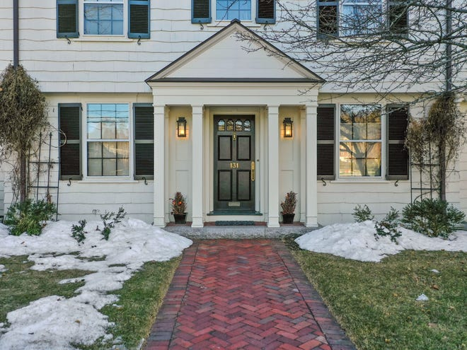 A herringbone brick walk leads to a portico with a front door with a row of decorative curved windows and attractive copper lanterns placed so that they are visible between the four elegant front columns.