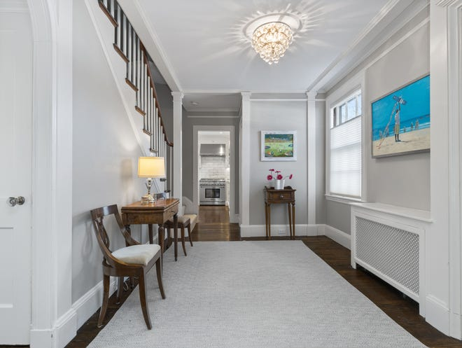 The spacious foyer has a turned staircase with an arched display niche that complements the arched doorway to the dining room.