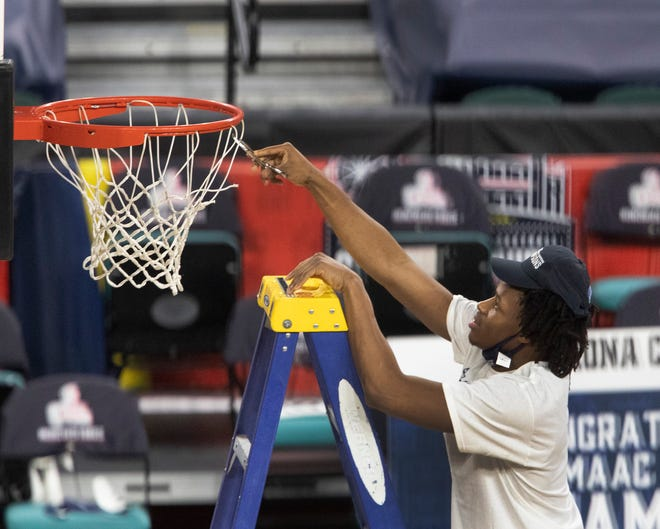 An Iona player takes his turn cutting down the net after winning the MAAC tournament.
