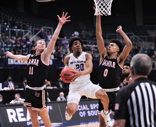 ACU's Coryon Mason (20) drives between Lamar's David Muoka (0) and Anderson Kopp (11) in the first half. ACU beat the Cardinals 93-71 in the Southland Conference tournament semifinals Friday, March 12, 2021 at the Merrell Center in Katy.