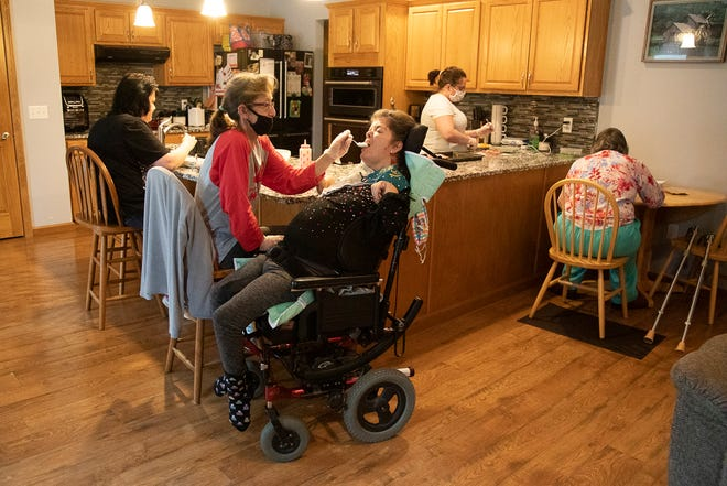 Angela Lansford helps feed Anne Marie Goode her dinner in Goode's house in Chillicothe. Lunsford, who has been a caregiver for Goode and her roommates, works for the Southern Ohio Adventures and Recreation (SOAR) program. The employees work with clients that have mental or physical disabilities.