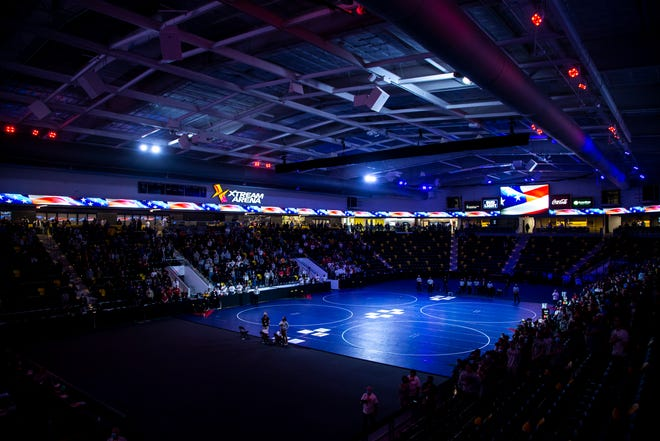 The four center mats are illuminated as the national anthem is played before the semifinals of the NWCA Division III Wrestling Coaches Association Championships, Saturday, March 13, 2021, at the Xtream Arena in Coralville, Iowa.