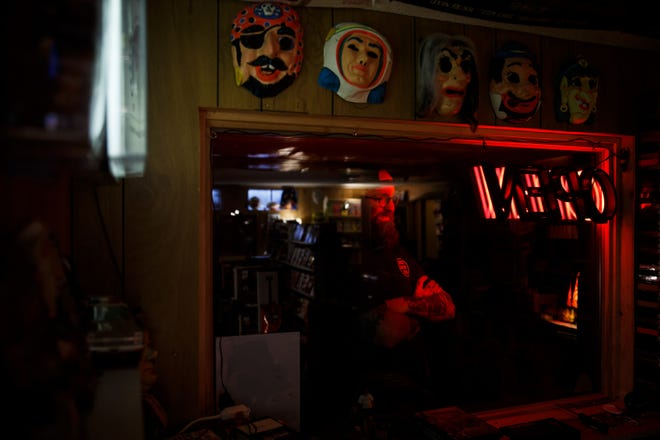 Brian Hogan poses for a portrait in his basement which he and his wife Erin have turned into a homage to the video rental stores they grew up going to on Thursday, March 11, 2021, in Urbandale, IA.