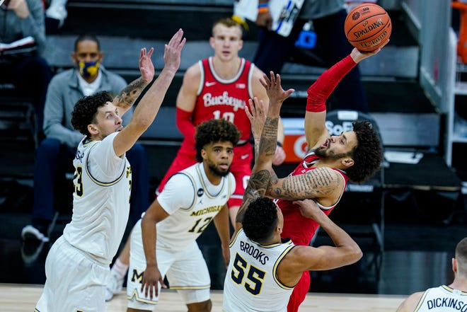 Ohio State guard Duane Washington Jr. shoots over Michigan guard Eli Brooks and forward Brandon Johns Jr. in the first half of the Big Ten tournament semifinal in Indianapolis on Saturday, March 13, 2021.