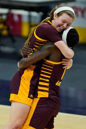 Central Michigan's Molly Davis, left, is hugged by Micaela Kelly after CMU defeated Bowling Green, 77-72, in the championship of the Mid-American Conference tournament on Saturday, March 13, 2021, in Cleveland.
