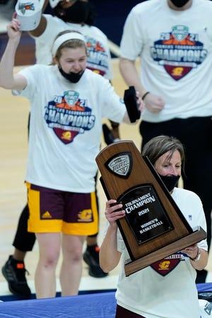 Pelatih kepala Central Michigan Heather Oesterle memegang trofi kejuaraan turnamen MAC.