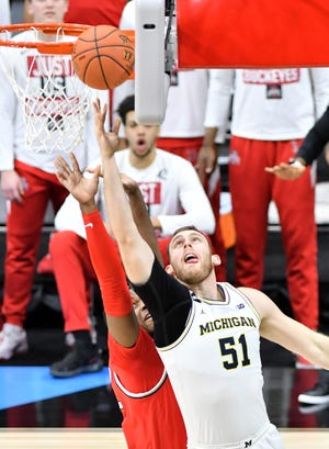 Penyerang Michigan Austin Davis (51) menempatkan keranjang di atas penyerang Ohio State EJ Liddell (32) di babak pertama.