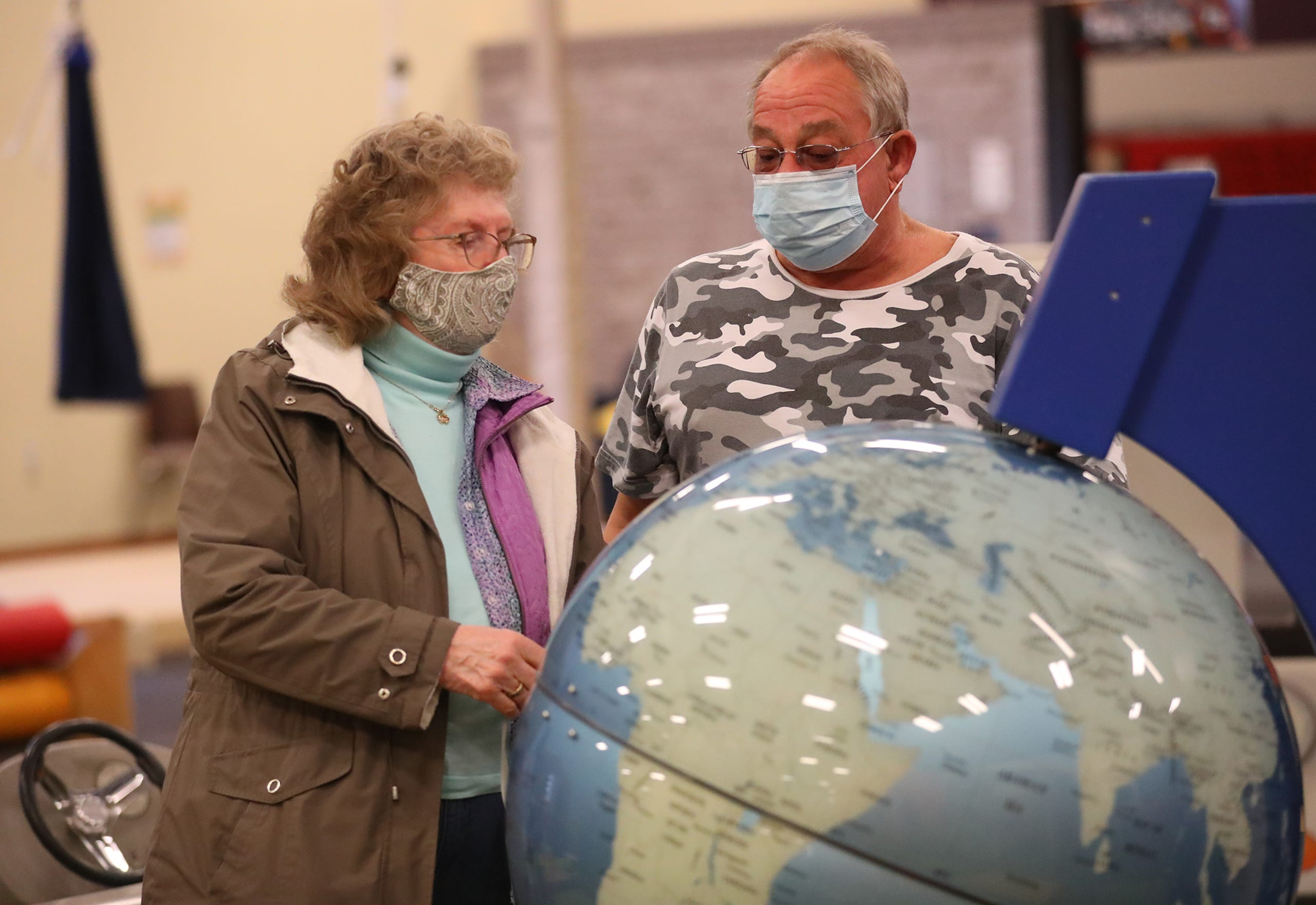 Angie Bodoh and Mark Brunelli of Fond du Lac look at a globe Saturday, March 13, 2021 at the Fond du Lac Children's Museum in Fond du Lac, Wis. The museum opens today to the public after being closed because of the Covid-19 pandemic. Doug Raflik/USA TODAY NETWORK-Wisconsin