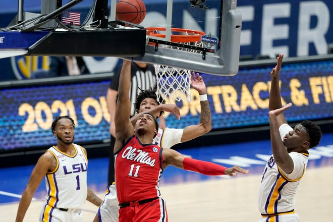 Mississippi's Matthew Murrell (11) lays in a shot between LSU defenders Ja'Vonte Smart (1) and Darius Days (4) in the first half of an NCAA college basketball game in the Southeastern Conference Tournament Friday, March 12, 2021, in Nashville, Tenn. (AP Photo/Mark Humphrey)