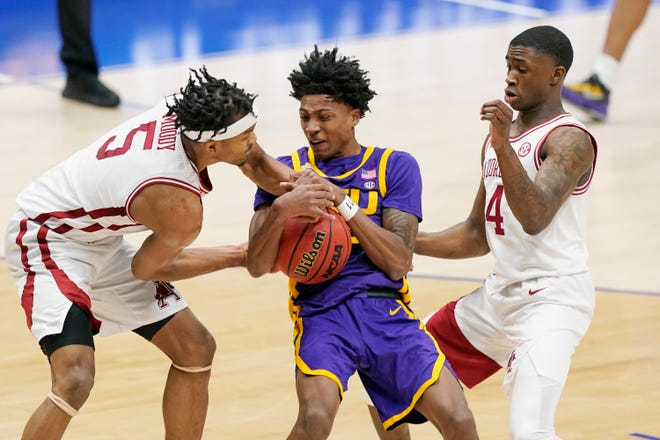 LSU's Eric Gaines, center, battles for the ball with Arkansas' Moses Moody (5) and Davonte Davis (4) in the first half of an NCAA college basketball game in the Southeastern Conference Tournament Saturday, March 13, 2021, in Nashville, Tenn. (AP Photo/Mark Humphrey)