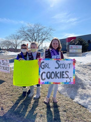 Girl Scouts have been running drive-thru events to sell cookies this year. Pictured promoting their sale in New Berlin are, from left, Nyla Olson, Samantha Klaas and Clare Shanahan.