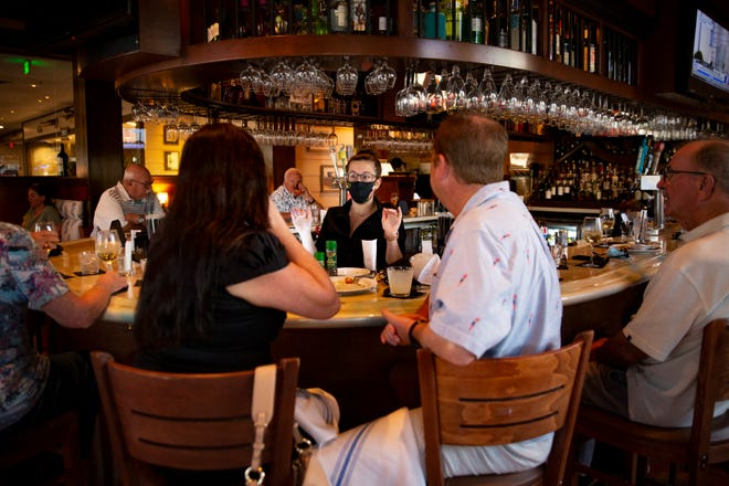 Bartender Cat Vigliano, center, speaks with her customers, Friday, March 12, 2021, at The Pearl Steak & Seafood Restaurant in North Naples.